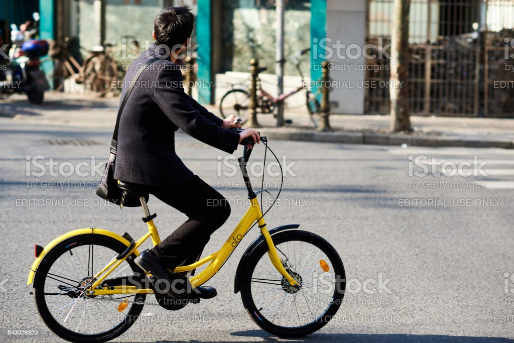 Young man riding an Ofo bicycle stock photo