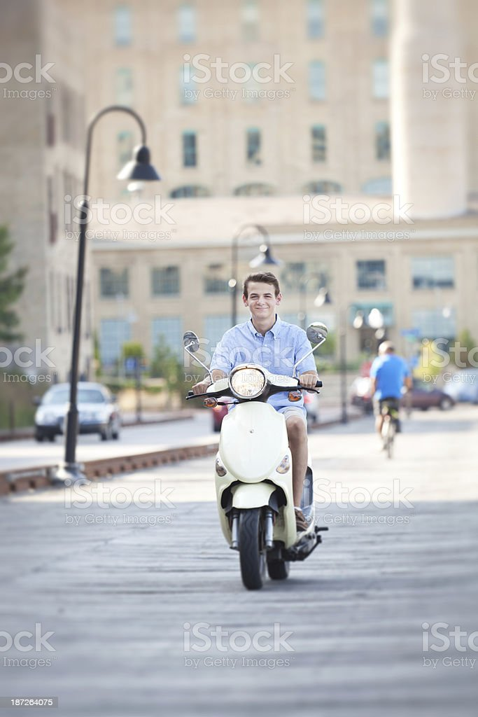 Young Man Riding Scooter on Urban Boardwalk by City Street royalty-free stock photo