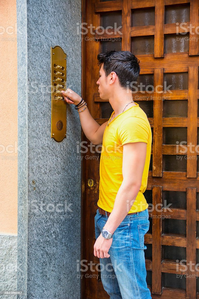 Young man ringing doorbell and talking on speaker phone stock photo