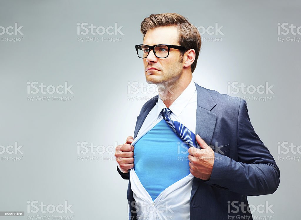 Young man ripping shirt open to reveal costume stock photo