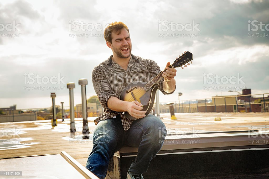 Young man rocking his mandolin on Brooklyn rooftop stock photo
