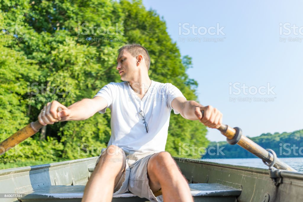 Young man rowing boat on lake in Virginia during summer in white shirt looking back stock photo