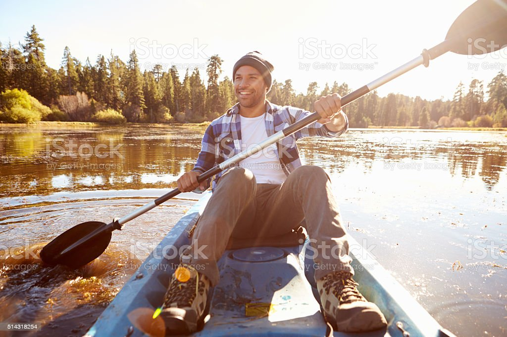 Young Man Rowing Kayak On Lake stock photo