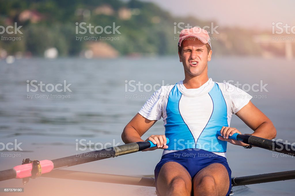 Young man rowing on the river close up shot stock photo