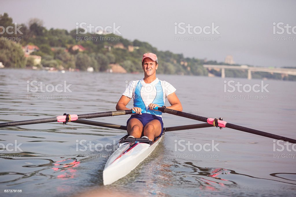 Young man rowing on the river stock photo