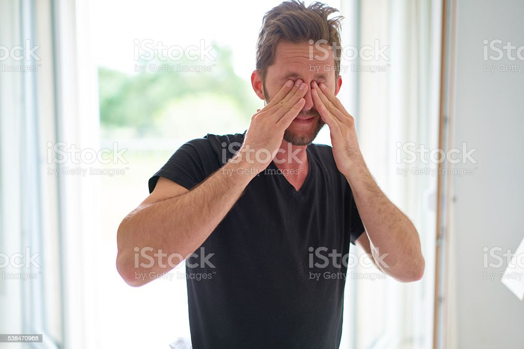 young man rubbing his eyes stock photo