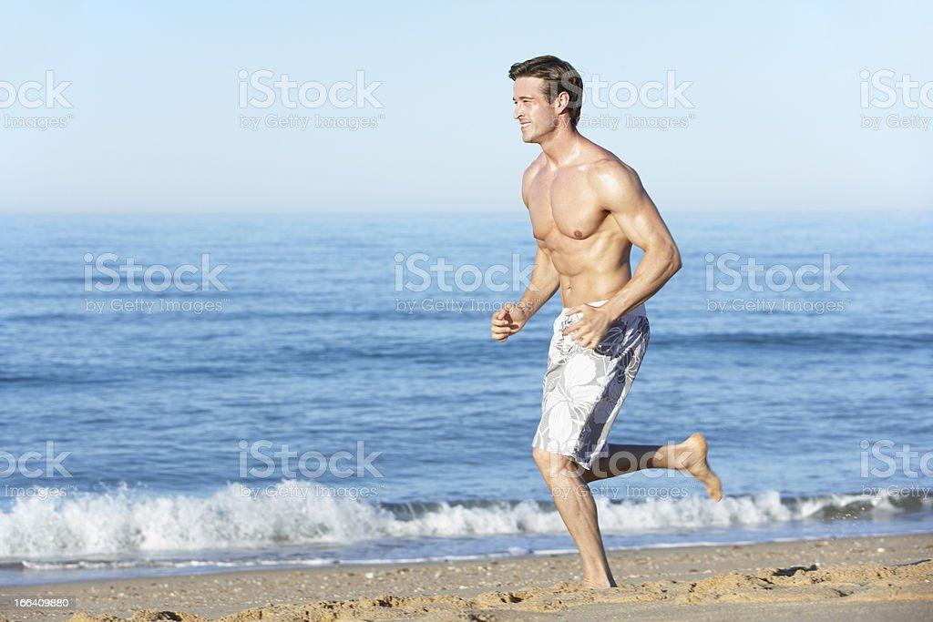Young Man Running Along Summer Beach royalty-free stock photo