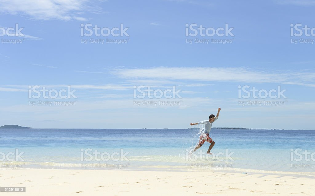 young man running in shallow water on tropical beach royalty-free stock photo