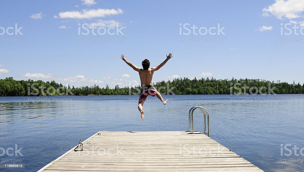 Young man running off dock on beautiful summer's day stock photo