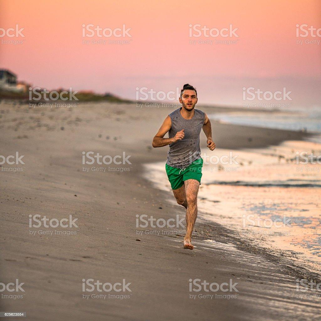 Young man running on Hampton Beach, Long Island, USA stock photo