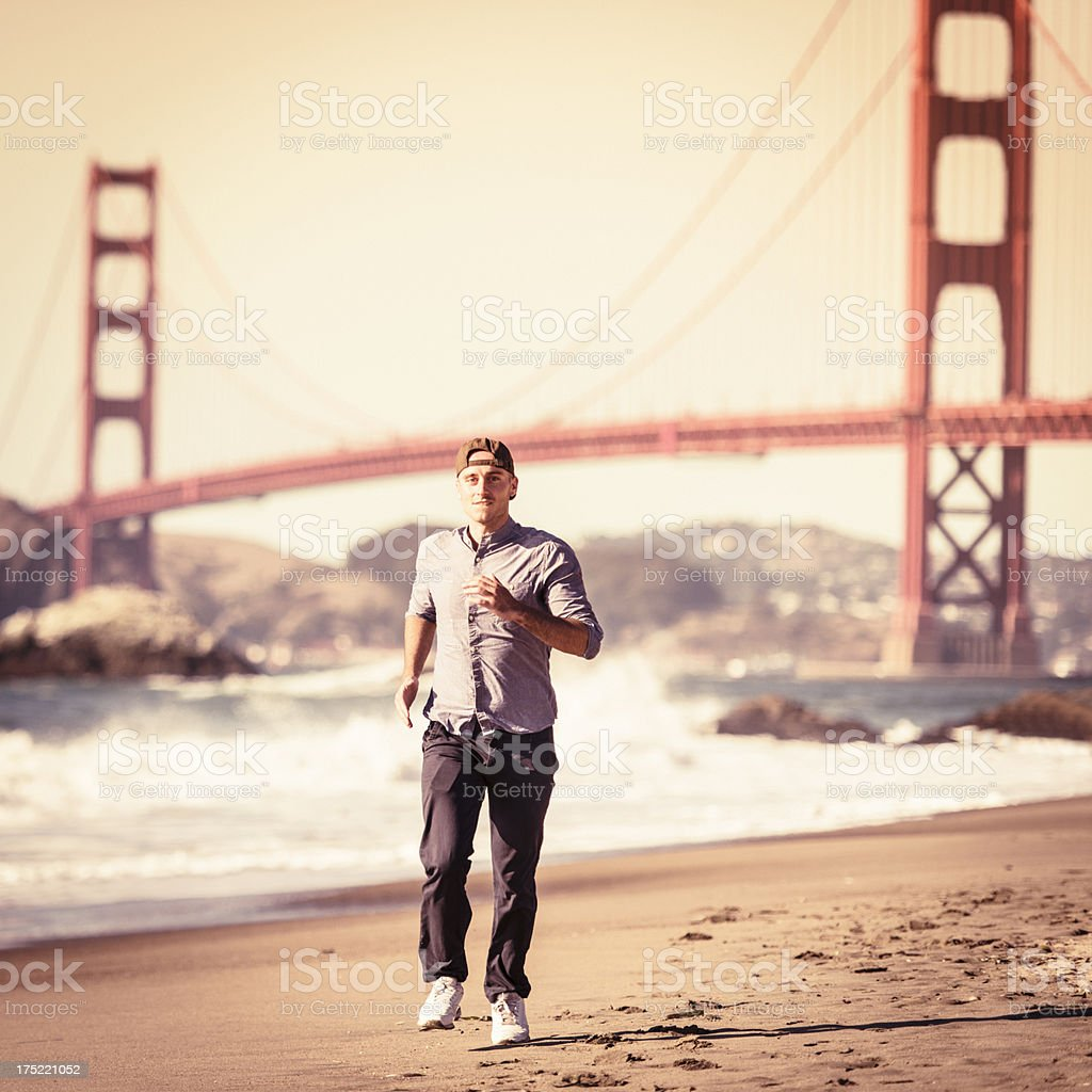 Young man running on the beach royalty-free stock photo
