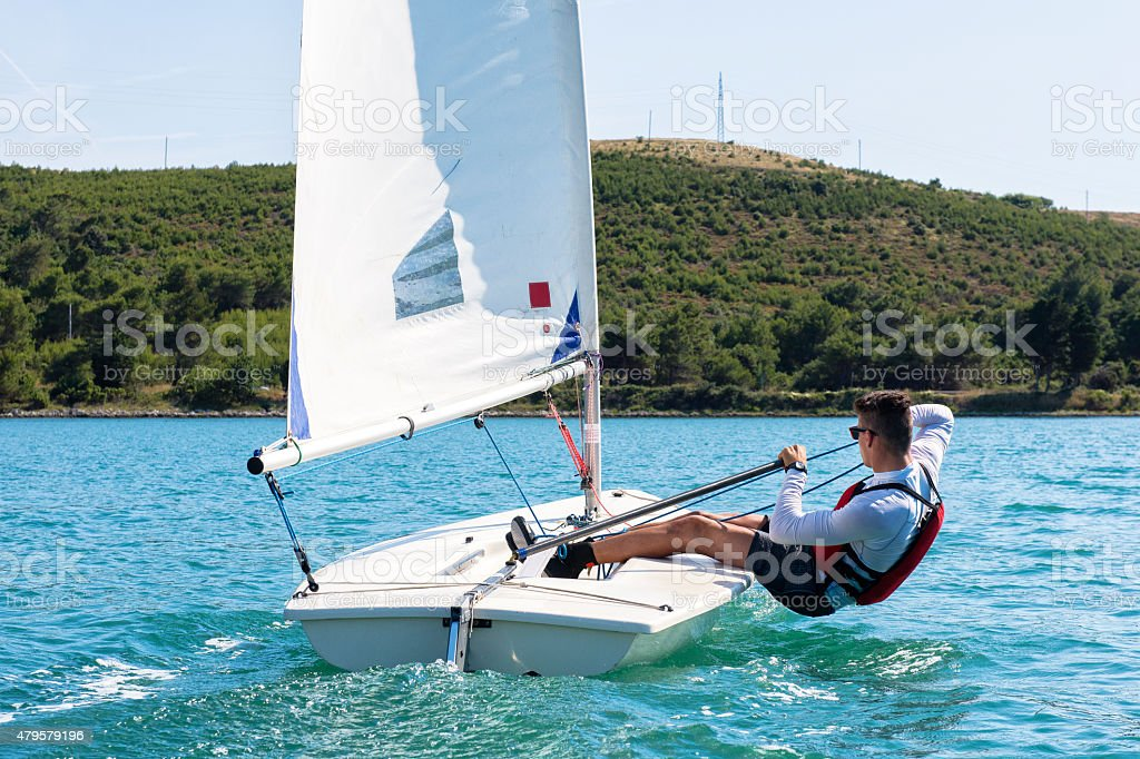 Young man sails a laser class sailing boat stock photo