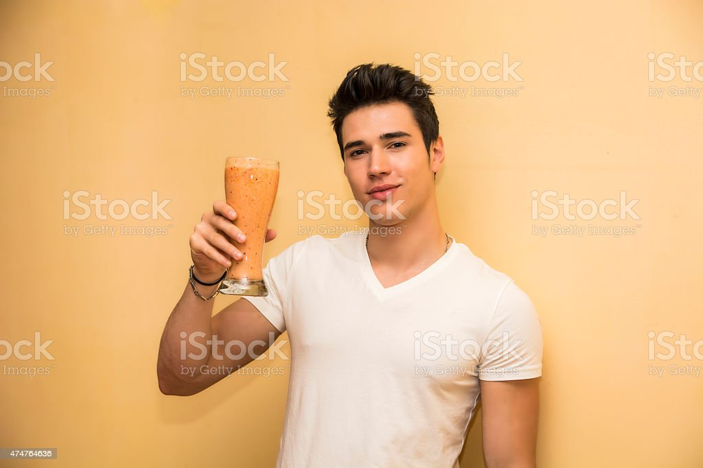 Young man saluting with a healthy drink stock photo