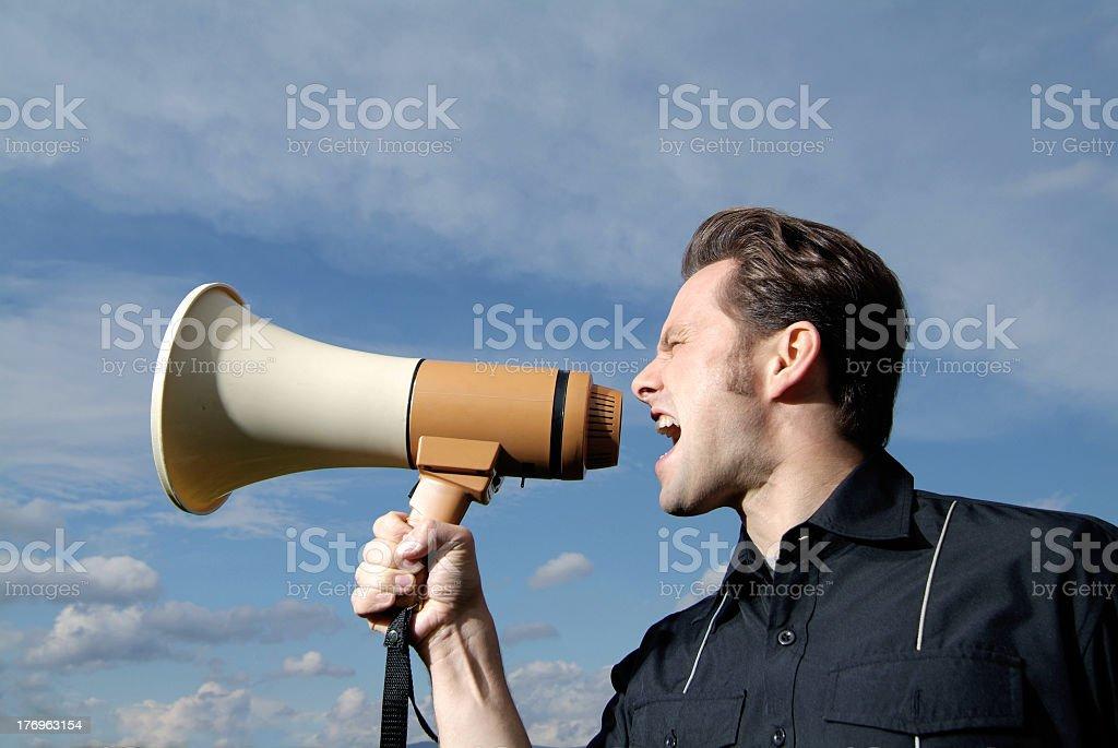 Young man screams into a big megaphone  stock photo