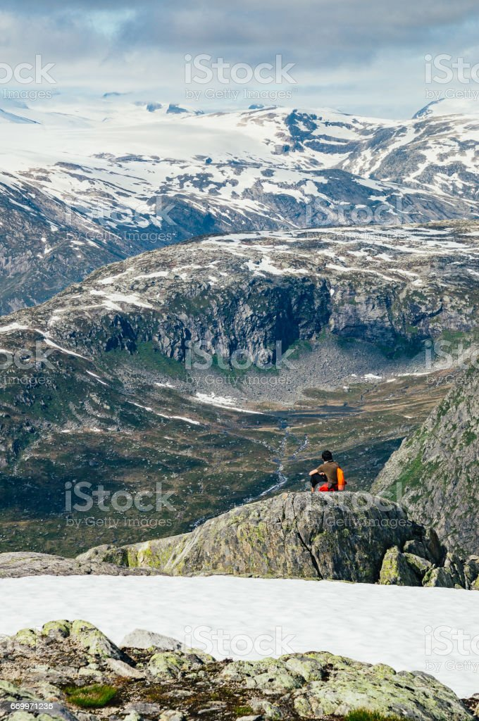 Young man seating on edge of mountain and enjoying wonderful view stock photo
