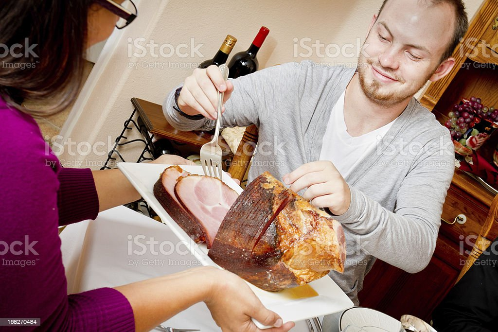Young Man Serving Ham at Holiday Dinner stock photo