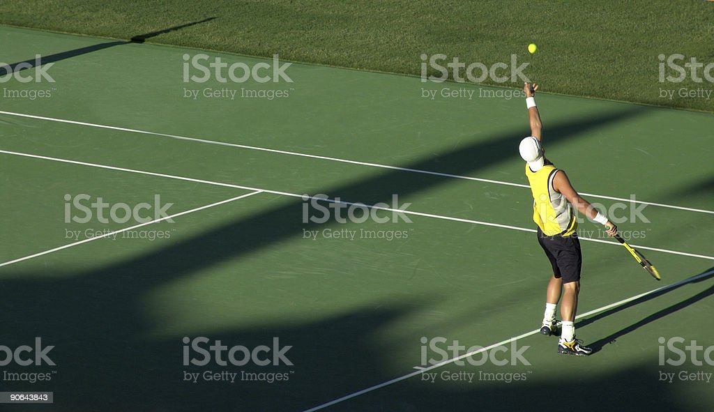 A young man serving the tennis ball stock photo