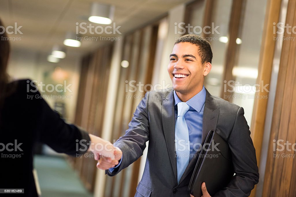young man shakes hands with his potential new boss stock photo