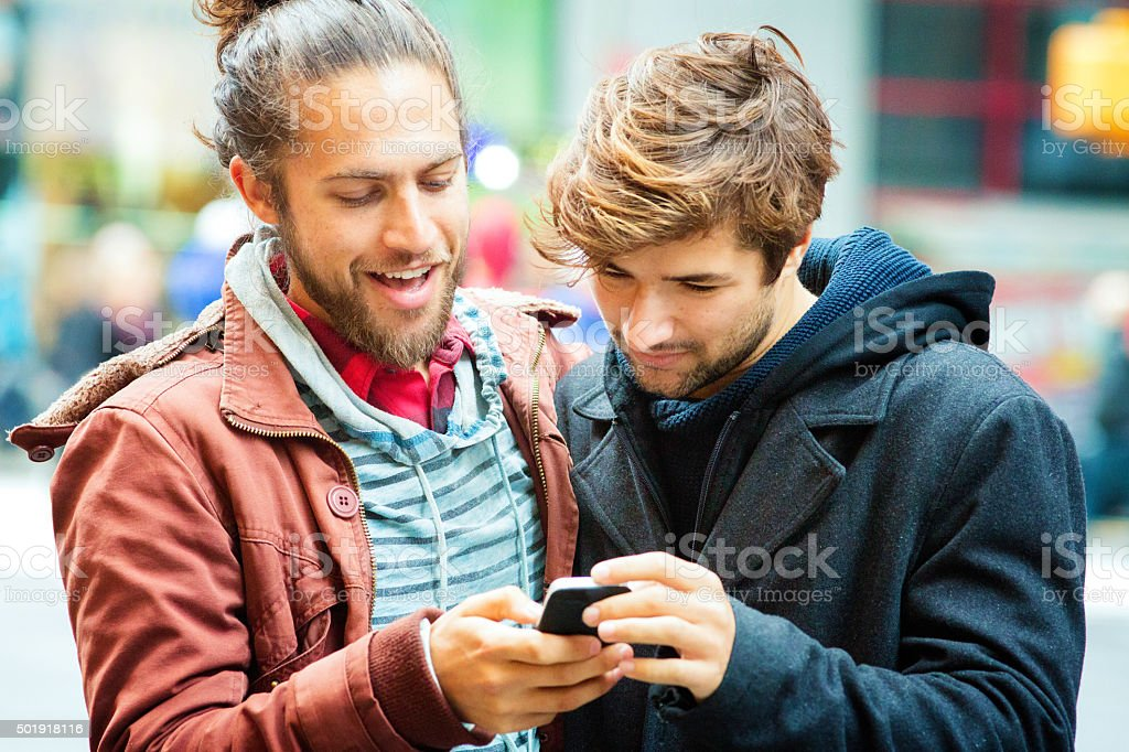 Young man sharing media with friend on mobile phone close-up stock photo