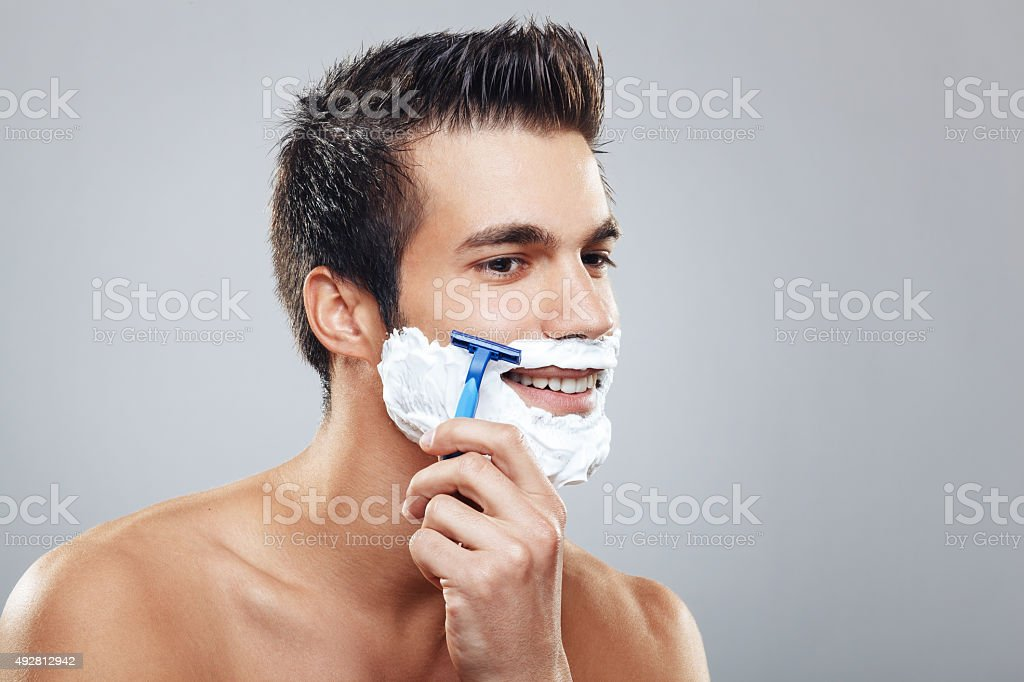 Young man shaving beard stock photo
