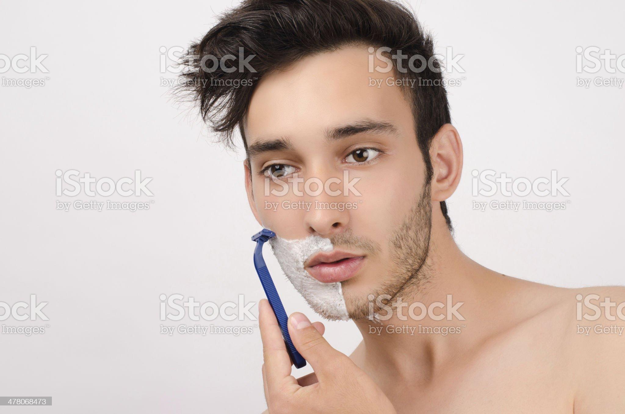 Young man shaving his beard royalty-free stock photo