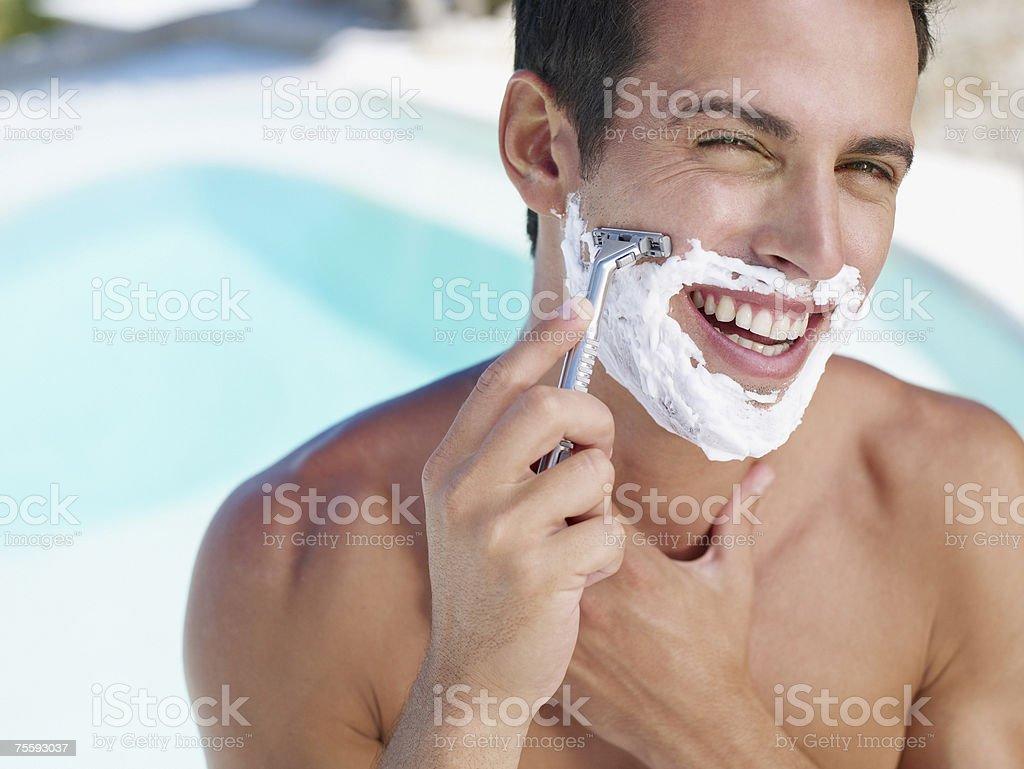 Young man shaving stock photo