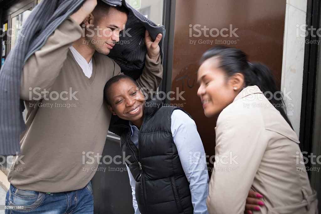 Young man shelters two women stock photo