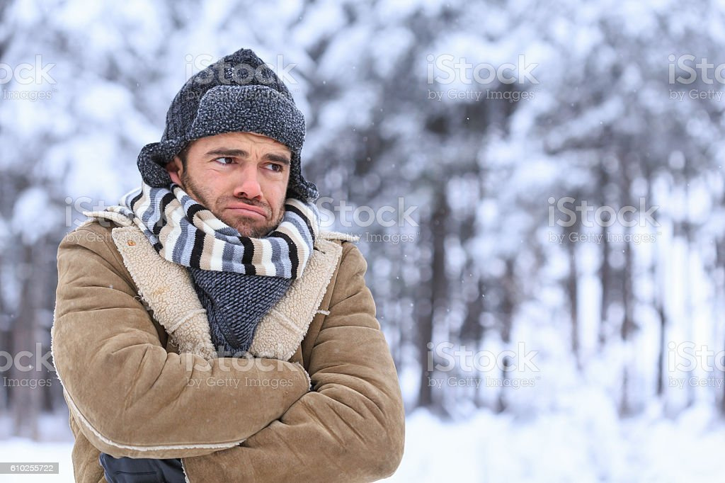 Young man shivering in snow forest stock photo