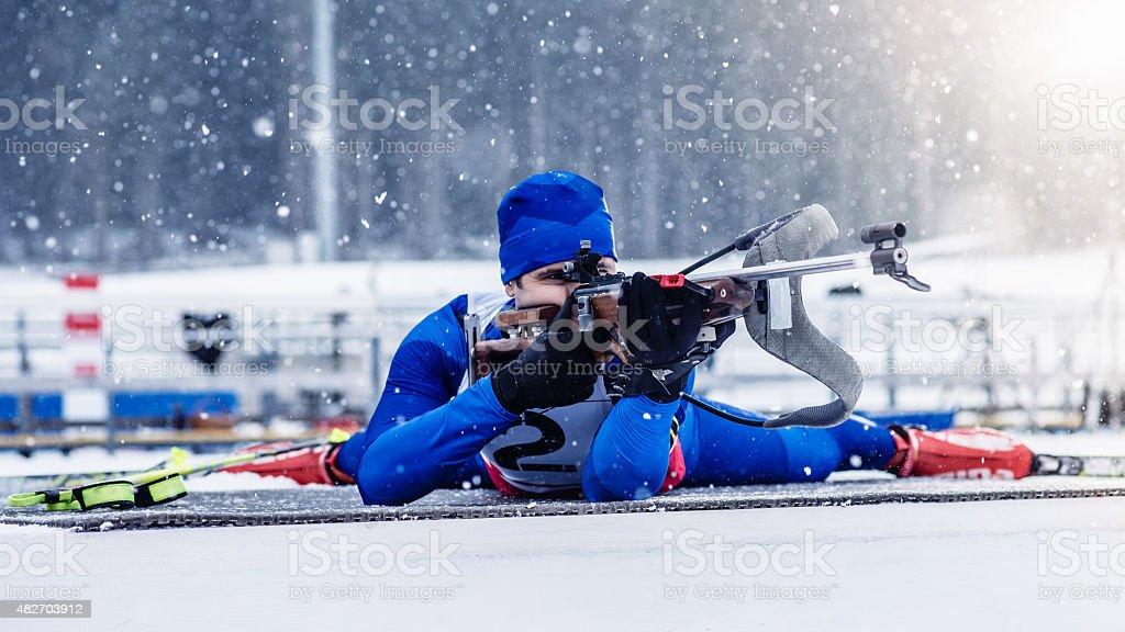 Young man shooting at biathlon training stock photo