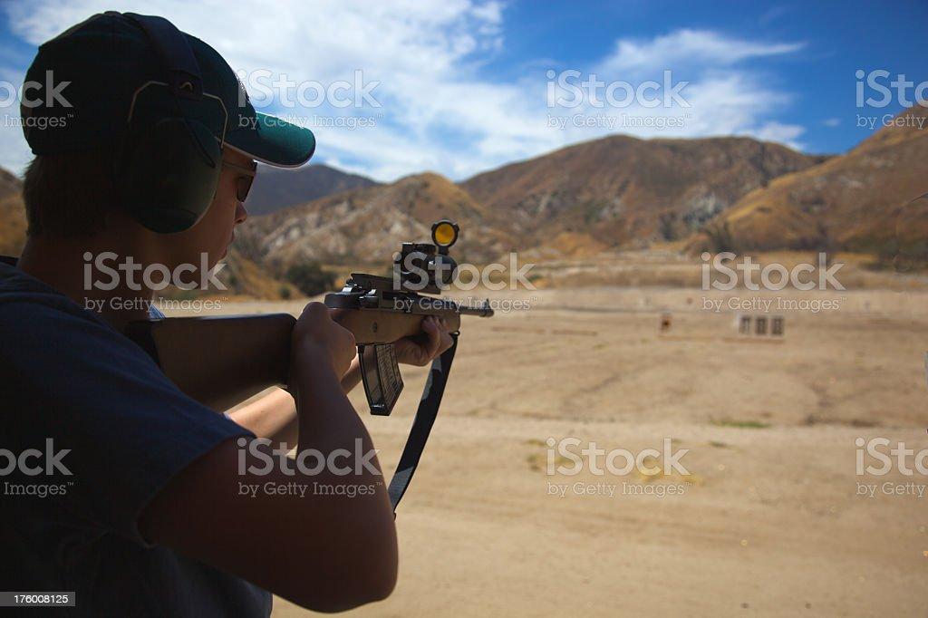 Young Man Shooting at Gun Range or Gun Club in Desert royalty-free stock photo