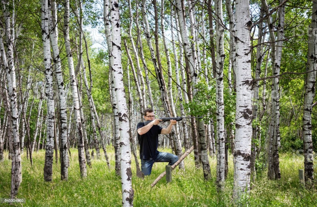 young man shooting his shotgun in the woods. stock photo