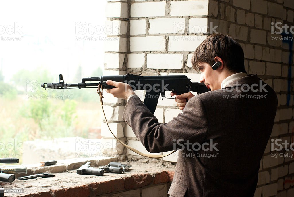 young man shoots from window stock photo
