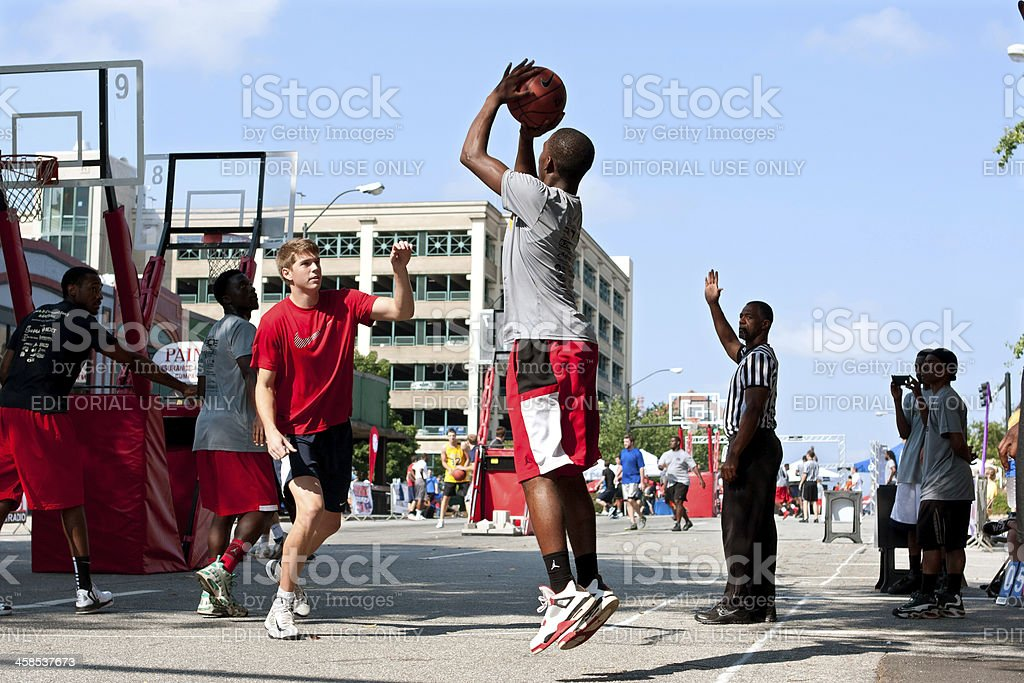 Young Man Shoots Jump Shot In Street Basketball Tournament stock photo
