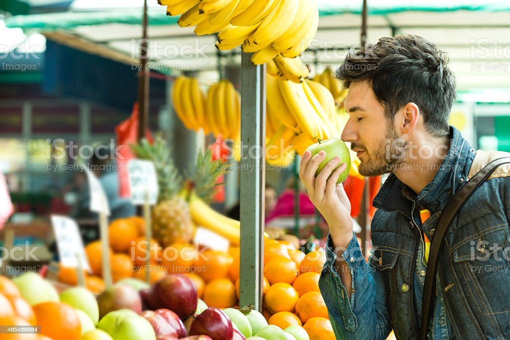 Young man shopping for fruits on the market stock photo