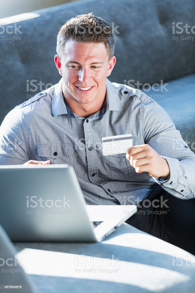 Young man shopping online, paying with creditcard stock photo