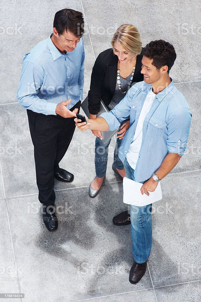 Young man showing a text message to a colleagues stock photo