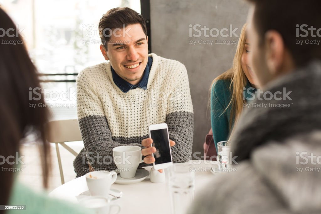 Young man showing his mobile phone in cafe stock photo