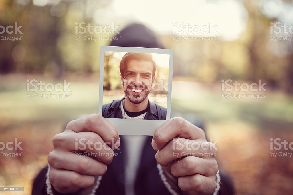 Young man showing instant photo stock photo