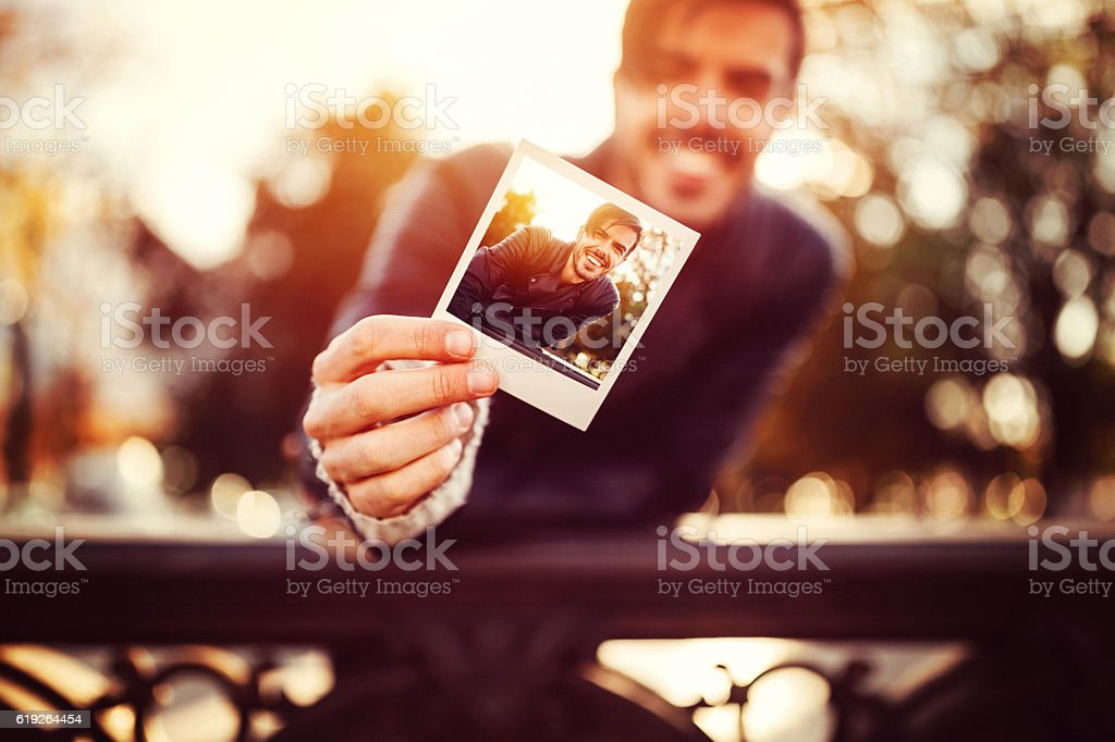 Young man showing instant selfie stock photo