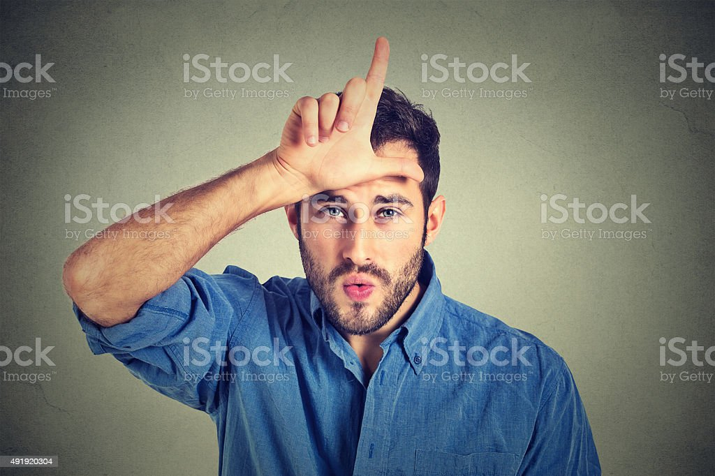 young man showing loser sign looking at you with disgust stock photo