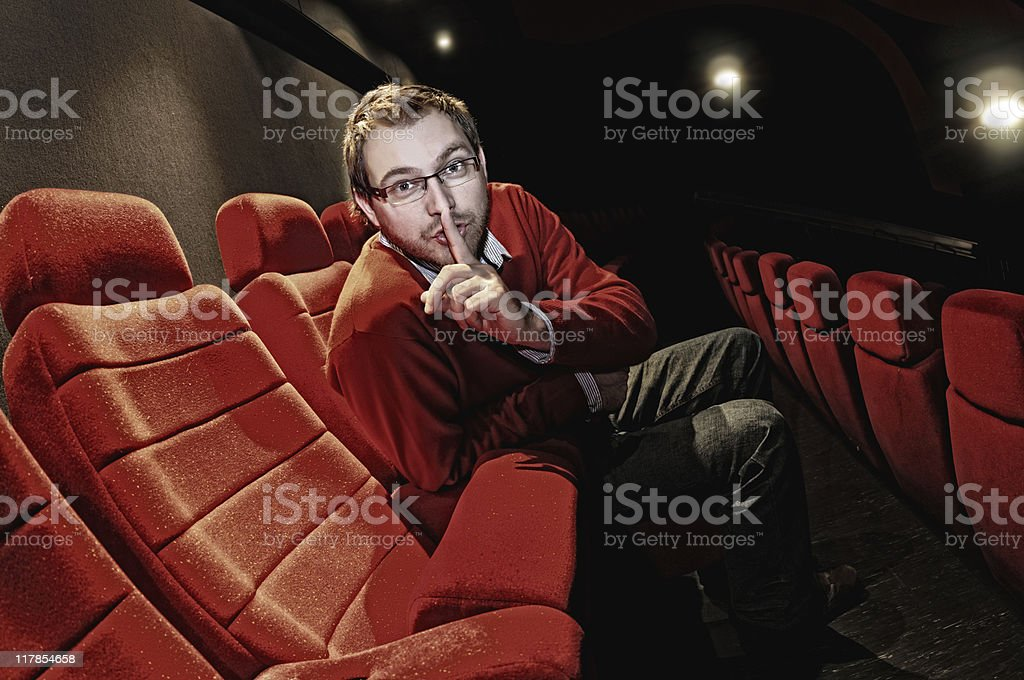 Young man showing silence on red seats stock photo
