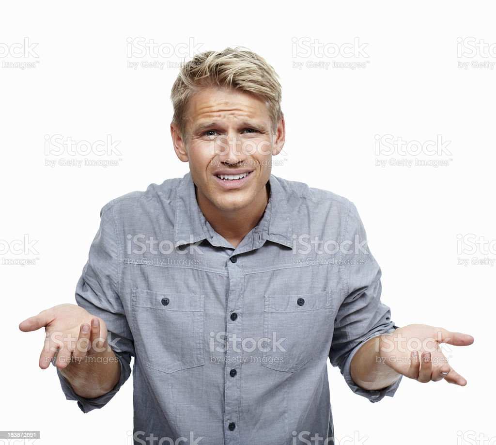 Young man shrugging in surprise royalty-free stock photo