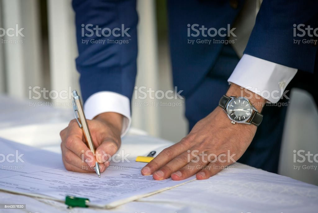 Young Man Signing a Document stock photo