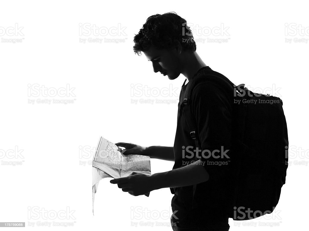 young man silhouette backpacker reading map royalty-free stock photo