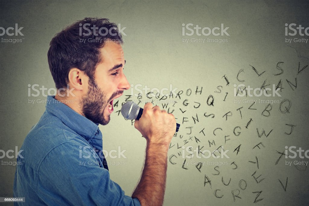 Young man singing in microphone with alphabet letters coming out of his mouth stock photo