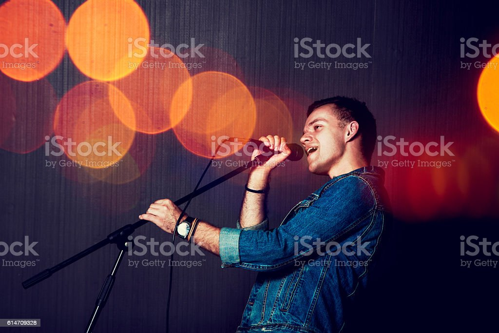 Young Man Singing with Microphone. stock photo