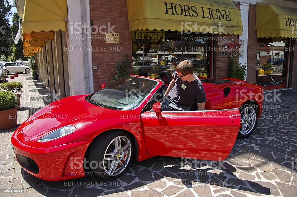 Young man sits into Ferrari F430 stock photo