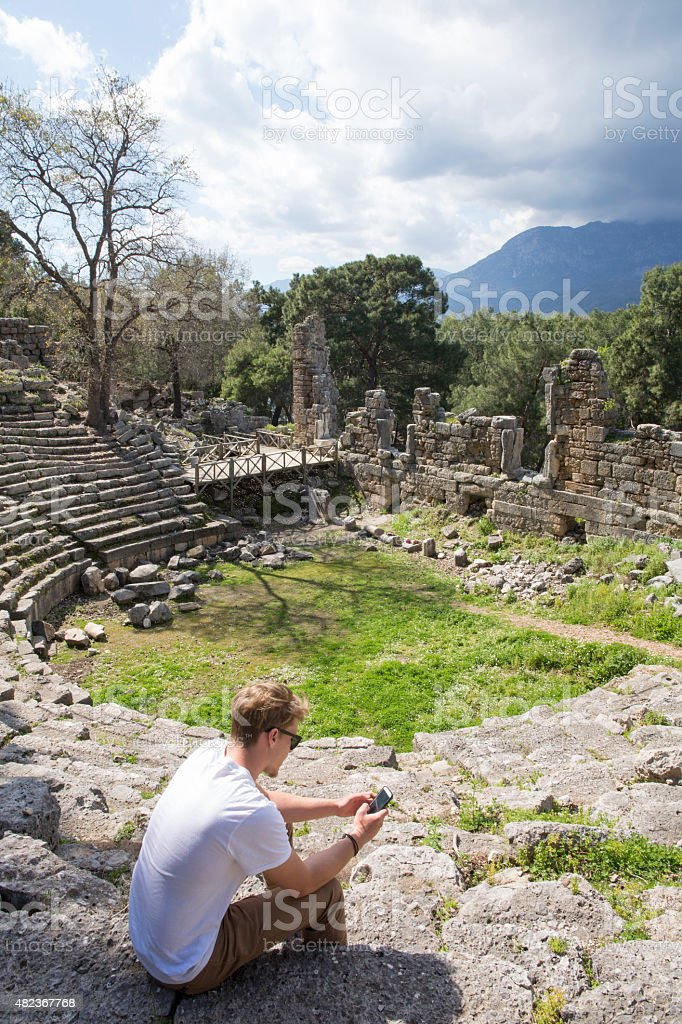 Young man sits on theatre steps of ancient Greek ruin stock photo