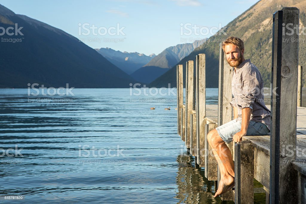 Young man sits on wooden pier above lake, relaxes stock photo