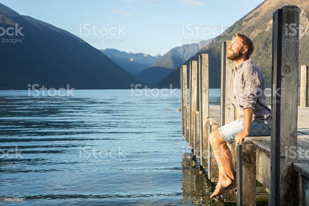 Young man sits on wooden pier at sunrise stock photo